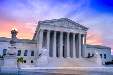 View of marble columns and greek classical architecture of the United States Supreme Court building with sunrise in background