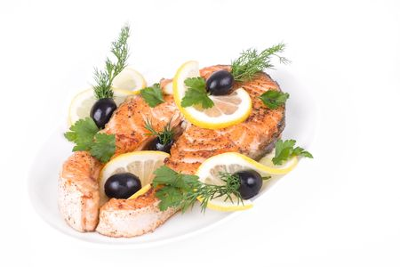 Appetizing Grilled Salmon with lemon, black olives and mixed greens isolated over white photo