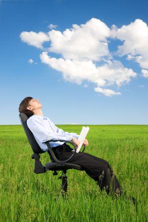 Businessman relaxing on green grassland under blue sky photo