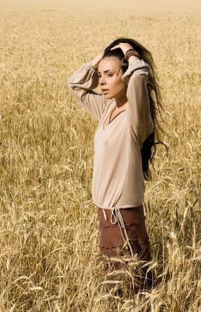 Attractive girl standing in wheat field and hold her head photo