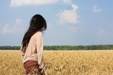 Hippie girl standing in wheat field rear view photo
