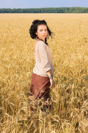 Young attractive girl standing in wheat field photo