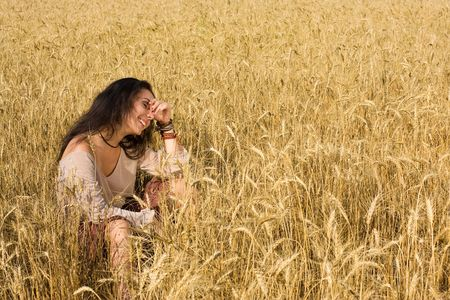 Attractive girl sitting in golden wheat field photo