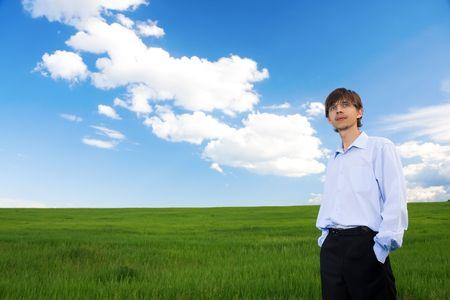Successful businessman standing on green grassland under blue sky photo