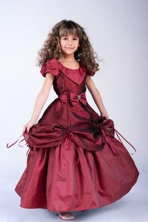 Beautiful little girl dancing in wine red dress photo