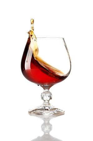 Splash van cognac in glas Stockfoto