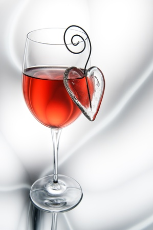 Glass of red wine decorated heart. photo