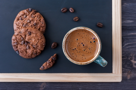 Slate chalk board with a cup of coffee and chocolate chip cookies photo