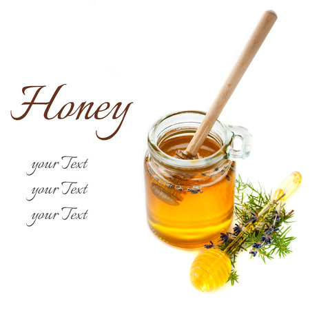 Glass jars of honey and a spoon of honey photo