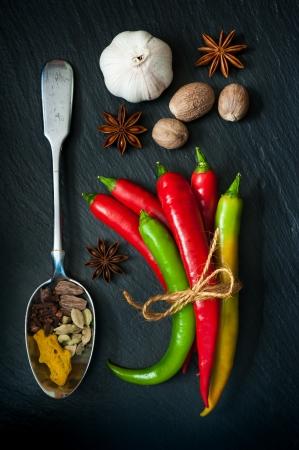Hot chili pepper, nutmeg, cardamom, turmeric, star anise on a dark background Standard-Bild