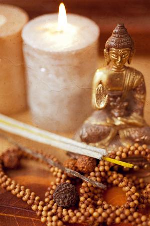 sandalwood: Statue of Buddha, incense, candles and rudraksha. retro style.