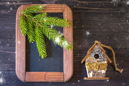 Christmas concept. Vintage chalk board, spruce branches and birdhouse photo