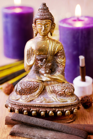 Statue of Buddha, incense, candles and rudraksha photo