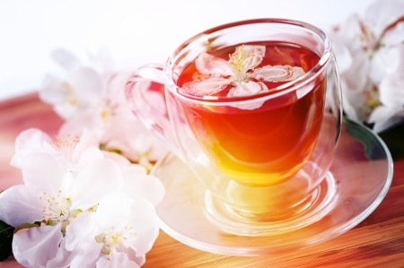 Herbal tea in a glass bowl with flowers of apple photo