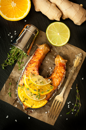 Grilled salmon, lime, orange and ginger on a black slate chalkboard photo