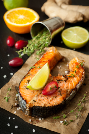 Grilled salmon fish with lime, thyme and orange on a black slate chalkboard. photo