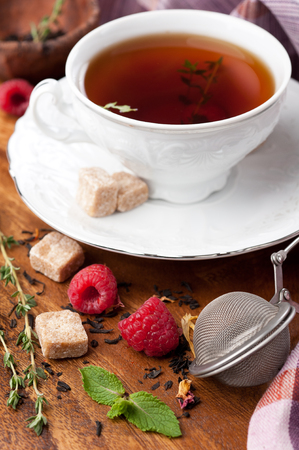 Tea with raspberries, fresh mint, thyme and brown sugar photo