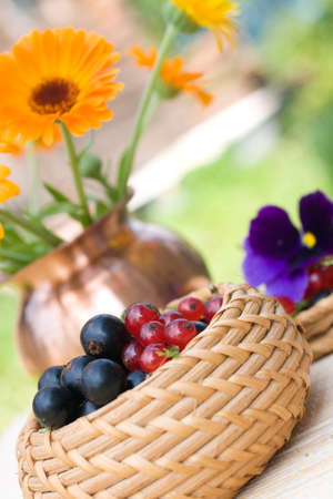 bast: Black and red currant in a basket and a calendula bouquet