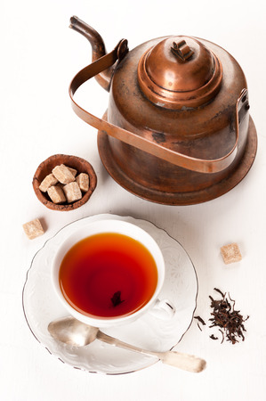 teakettle: Cup of tea with brown sugar and a vintage teapot Stock Photo