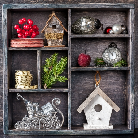 Christmas decorations set: antique clocks, birdhouse, Santas sleigh and Christmas toys in an old wooden box