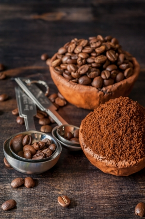 Ceramic bowl with coffee beans and ground coffee on a wooden background