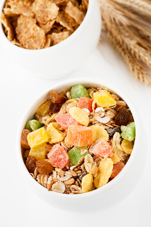 Granola (muesli flakes) with dried fruit in a bowl and ears of wheat photo