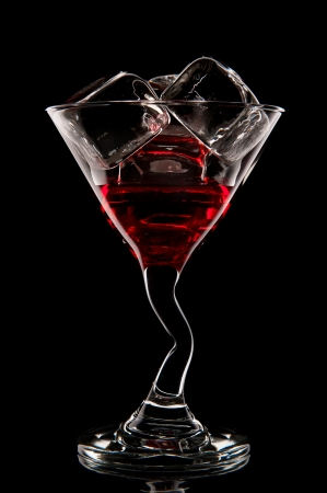 Red cocktail. Liquor, martini or cosmopolitan in a glass on a black background.
