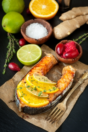 Grilled salmon with thyme on a dark background