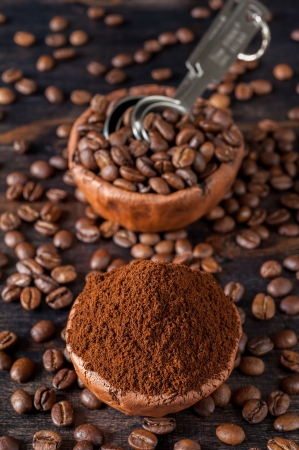 Vintage bowl with coffee beans and ground coffee on a wooden board