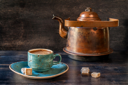 Espresso coffee in a blue cup and  old kettle on a wooden board
