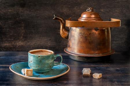 Espresso koffie in een blauwe kop en oude ketel op een houten plank