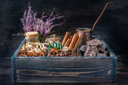 coffee beans, chocolate, cinnamon, star anise and honey in a wooden box on a vintage wooden background photo