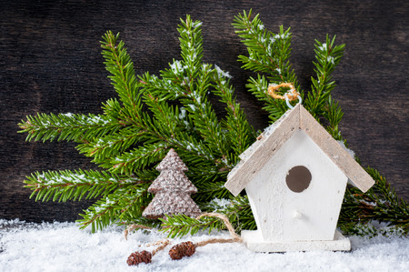 Сhristmas tree decoration and birdhouse on a wooden background photo