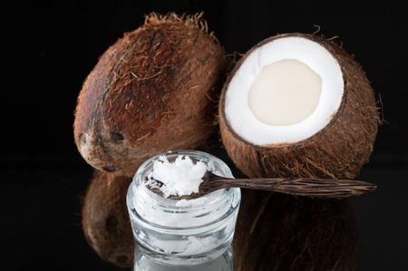 Kokosolie en kokosnoten op een zwarte achtergrond Stockfoto