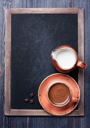 Cup of coffee with milk on vintage chalkboard photo