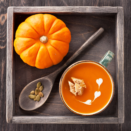 Pumpkin soup with croutons in a cup in vintage box Standard-Bild