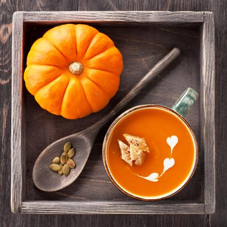 Pompoen soep met croutons in een beker in uitstekende doos