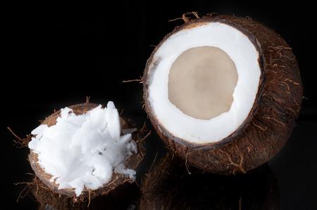 coconut oil: Olio di cocco e cocco alzato su sfondo nero Archivio Fotografico