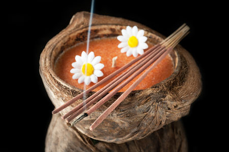 incense sticks: Aroma candle in coconut and incense sticks. The concept of meditation and relaxation
