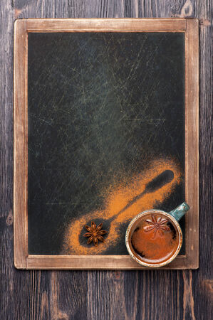 Cup of coffee with spices on vintage slate chalkboard. Design for the menu. photo