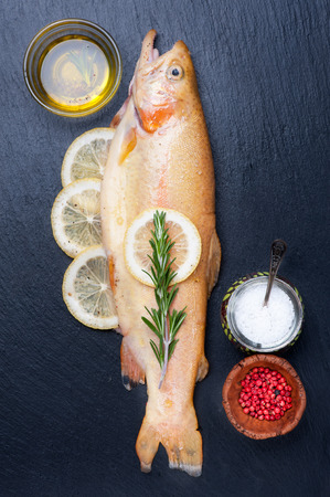 raw fish: Raw fish golden trout with herbs and spices on chalkboard