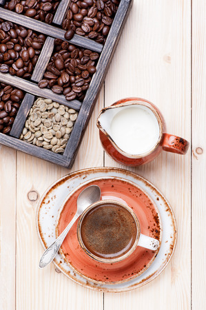 Espresso cup with milk and coffee beans in vintage box photo