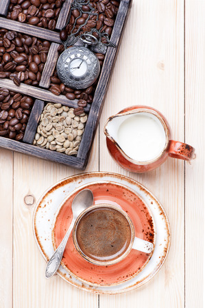 Cup of coffee with milk and  old box with coffee beans photo