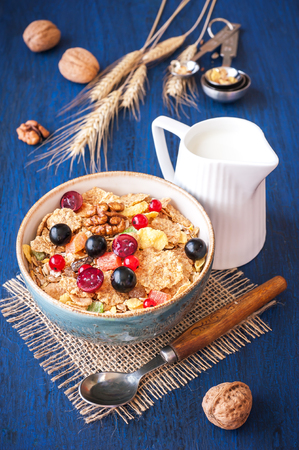 Muesli (granola) with berries, walnuts and milk on blue background photo