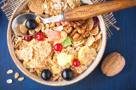 Close-up of muesli (granola) with berries, walnuts and milk on blue background photo