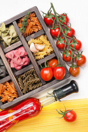 Mix Italian pasta and spaghetti tomatoes in wooden box  photo