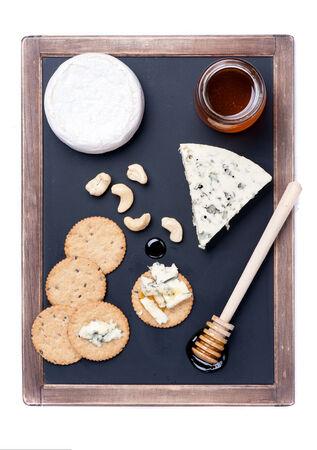 tabla de quesos: Tabla de quesos. Queso azul y queso camembert en la pizarra.