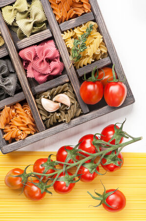 Assorted Italian pasta and spaghetti tomatoes in  wooden box  photo