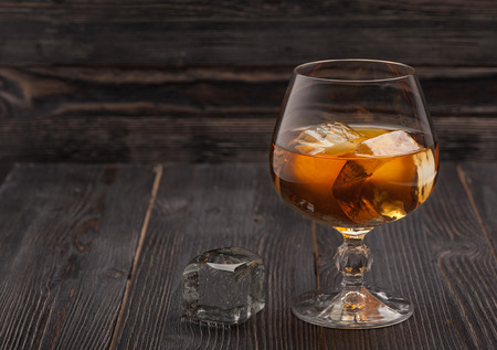 celebration party: Whiskey with ice on dark wooden background