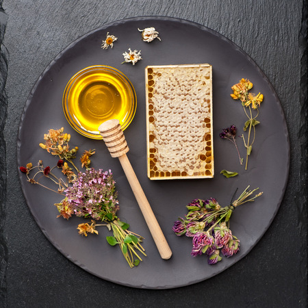 Honey, honeycomb and dried herbs on dark background